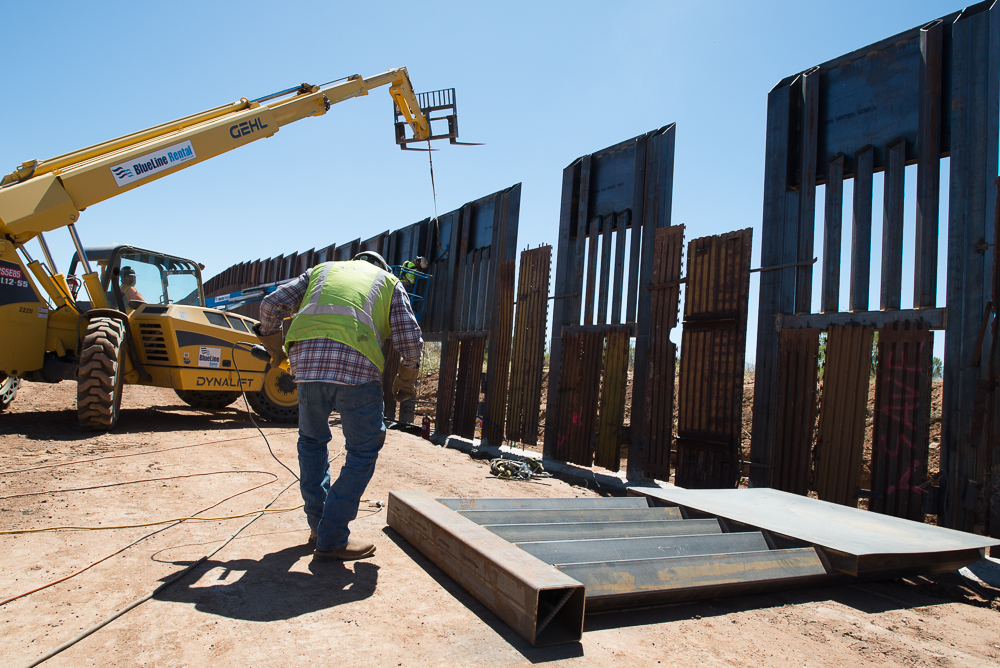 Construction workers use a crane to place a new segment of border wall near Naco, Arizona.